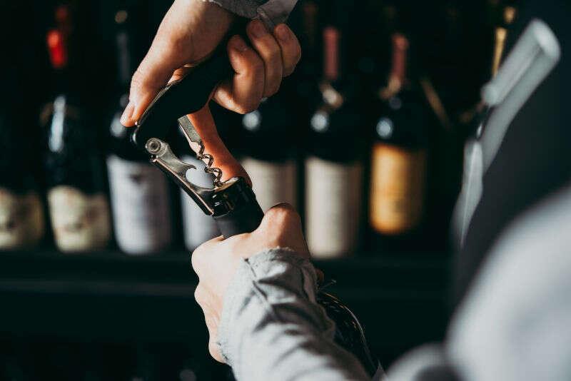 Sommelier apre una bottiglia con il tirabuscio