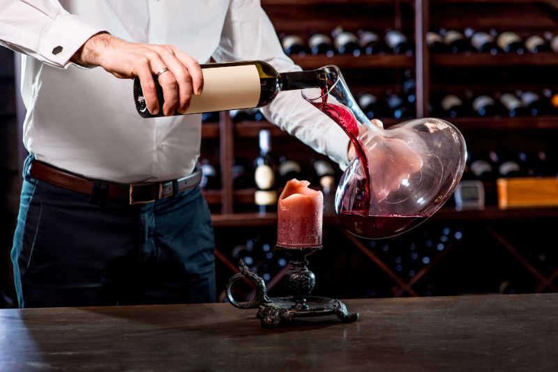 Sommelier versa il vino nel decanter in cantina
