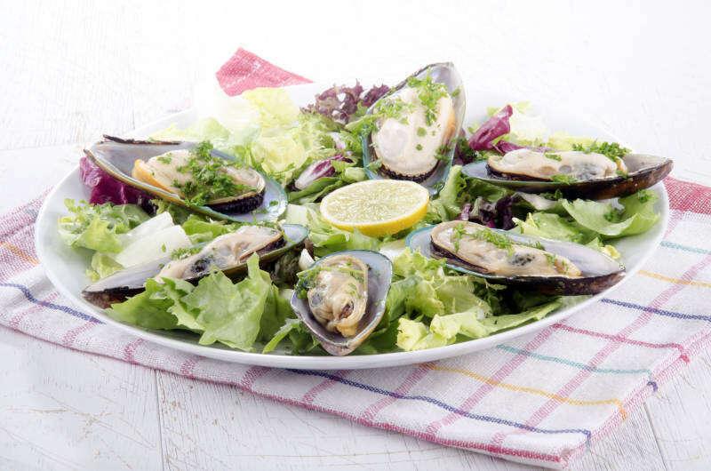 Cozze dalle labbra verdi della Nuova Zelanda con insalata e limone su un piatto