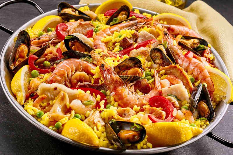 Paella con gamberi e cozze con riso giallo, piselli e peperoni