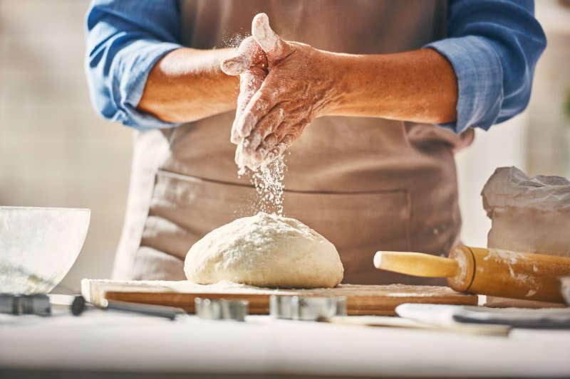 Panettiere lavora la pasta di pane con la farina