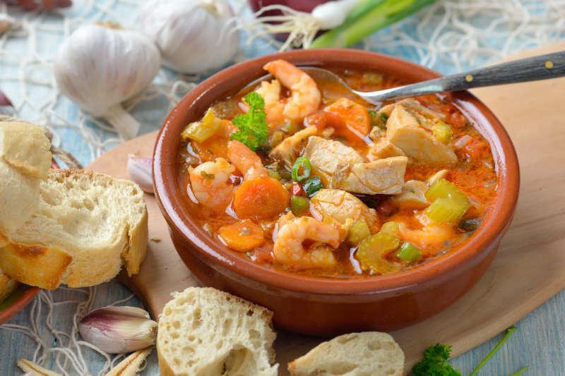 Zuppa di pesce mediterranea servita con pane bianco