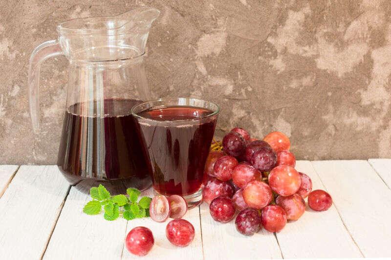 Brocca di succo d'uva e un ramo di uva