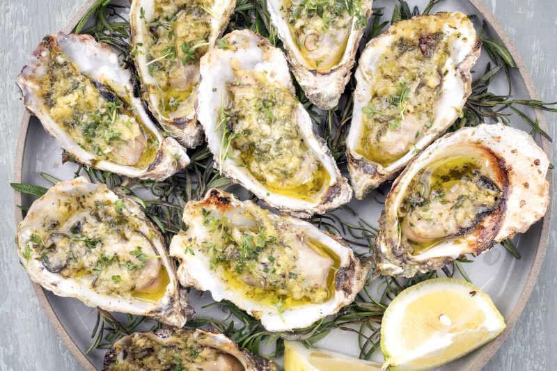 Ostrica aperta fresca cotta al forno con aglio, limone ed erbe aromatiche